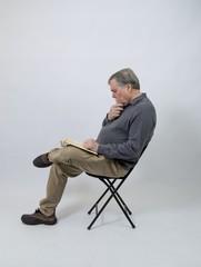 Senior bearded man reading isolated on white