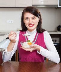 Smiling woman eating boiled rice at table