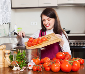 Smiling  woman cooking with tomatoes
