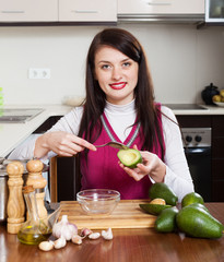 young woman cooking with avocado