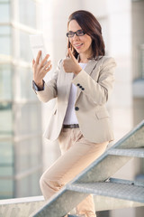 Businesswoman holding digital tablet with her thumb up