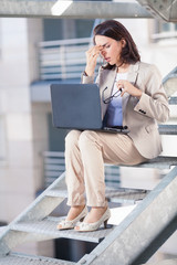 Young businesswoman tired of working on laptop