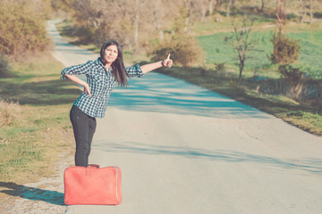 young woman standing o the road hitchhiking