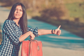 beautiful young woman hitchhiking on the road with a case