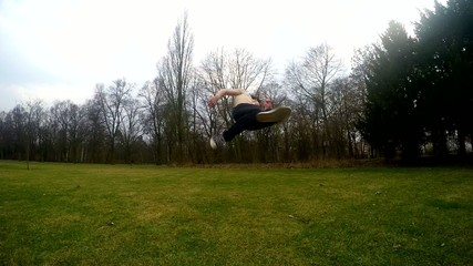 Guy jumps backflip in the park, slowmotion
