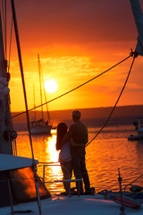 Couple in love on sailboat at sunset