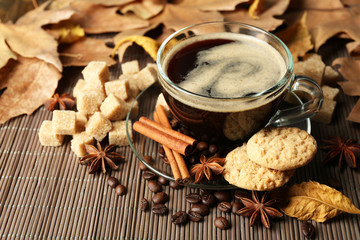 Glass cup of coffee, tasty cookies and autumn leaves