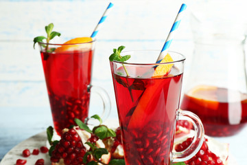 Pomegranate drink in glasses with mint and slices of orange