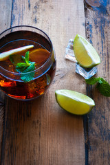 Cuba Libre Drink with lime on a wooden tabl
