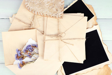 Old envelopes with photo papers and dry flowers