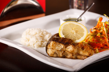 grilled fish and rice with many vegetables