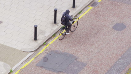 Young man in hooded sweatshirt cycling through an urban area
