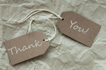 Two Beige Labels With Text Thank You Paper Background