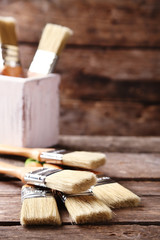 Paint brushes on old wooden background