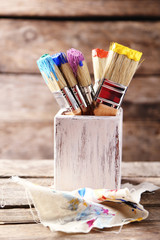 Brushes with colorful paints on old wooden background