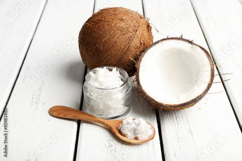 Coconut with coconut oil in jar on wooden background - 80483860