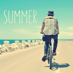 young man riding a bike and text summer, with a filter effect