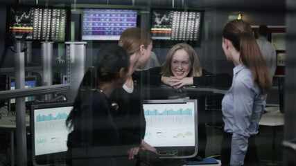 Casual team of financial traders take a break from work to chat together
