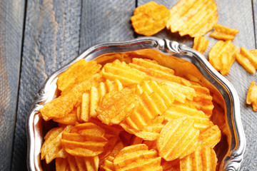 Delicious potato chips on plate on wooden table close-up