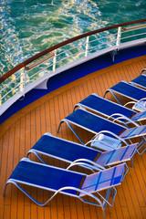 Blue sunbeds aligned on the deck