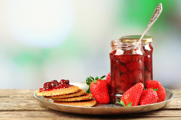 Jars of strawberry jam with berries and wafers