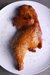 Smoked chicken leg on plate on table close up