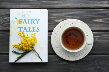 Fairy Tales book with cup of tea and sprig of mimosa