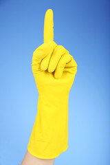 Rubber glove on hand, on blue background
