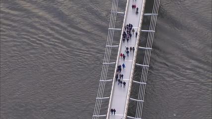 Aerial view of pedestrians crossing London's Millennium bridge