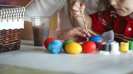 Kid painting Easter eggs with their mother