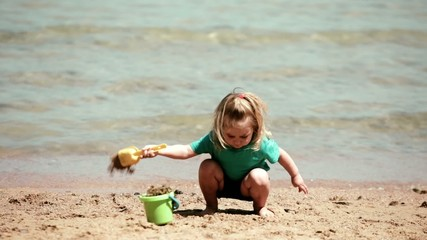 Baby girl playing dig on the beach of sand sea with a bucket and