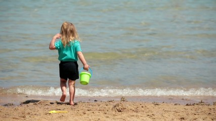 Baby girl playing on the beach of sand sea with a bucket and