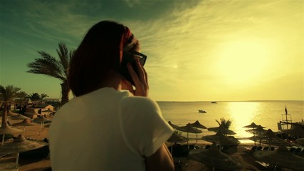Young beautiful happy woman talking on the phone at sunset or
