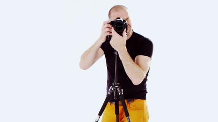 Professional photographer at work in his studio shooting against a white backgro