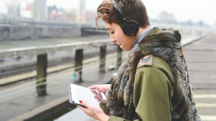 young beautiful short hair hipster woman in town using tablet te