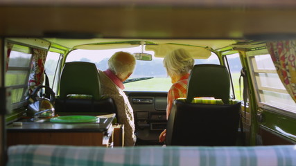 Attractive mature couple in camper van lean over to share a kiss