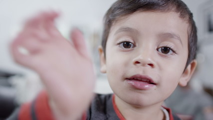 Little boy in close up waving directly to camera