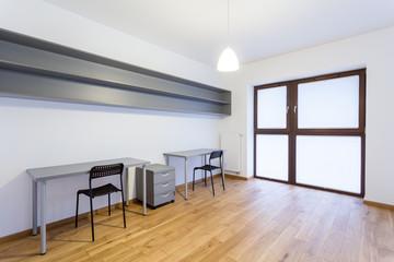 Gray desks in empty interior