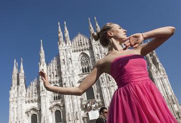 Pretty dancer wearing pink dress and posing in Milan