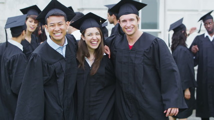 Portrait of happy student graduates stand together outside university building
