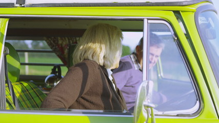 Attractive couple in camper van lean over to share a kiss