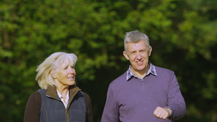 Happy mature couple walking in the countryside on an autumn day
