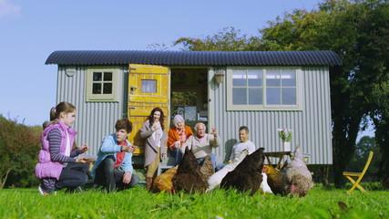 Extended family group feeding chickens outside quaint caravan