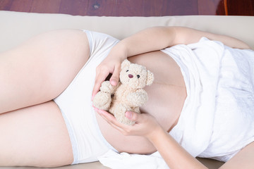 pregnant woman with hands and have bear doll