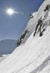 Snowboarder springt von einem Felsen