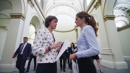 Young female business delegates stand and chat in busy conference building