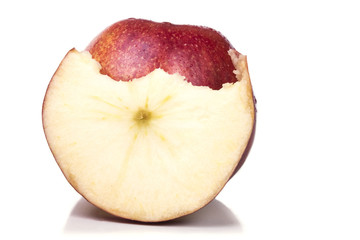 One ripe red apple with a slice bitten