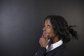 African or African American woman teacher on chalk black board