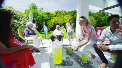 Diverse group of family & friends enjoy refreshment in the garden on a sunny day