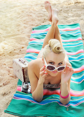 attractive young woman lying on the beach with vintage colorful